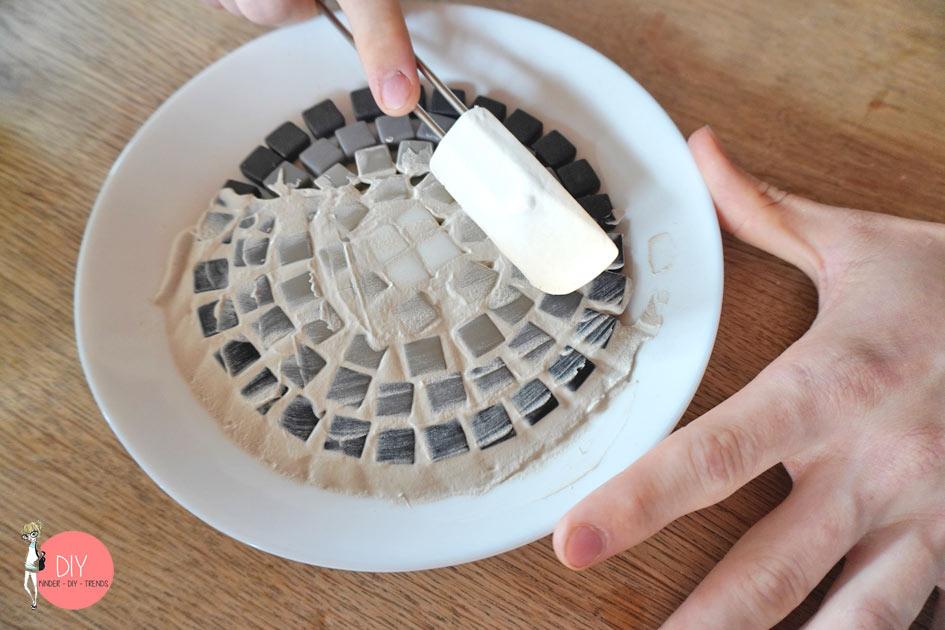 Zwischen den Mosaiksteinen ausfugen mit Fugenmasse und Spatel