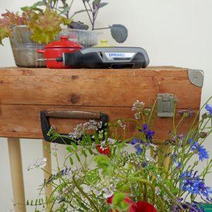 Koffer auf vier Rundhölzer schrauben: DIY Pflanztisch selber machen
