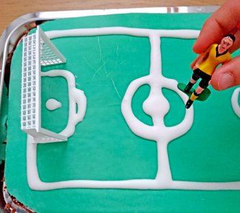 Tippkick Figur auf den Fußball WM Kuchen stecken