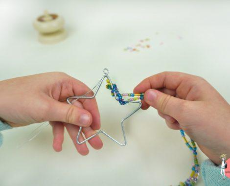 Perlen mit der Perlenmühle auffädeln, dann um einen Drahtstern wickeln