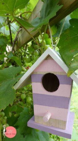 DIY Vogelhaus in rosa lila Kreidefarbe mit weißem Dach als Gartendeko